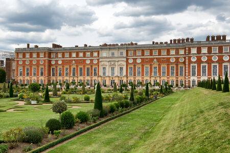 orden judicial: Vista pintoresca de Hampton Court Palace, Londres, Reino Unido mirando a través de los jardines bien cuidados en la fachada renacentista señorial