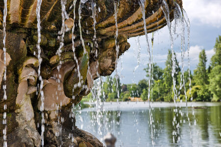 overflowing: Ornamental stone fountain covered in moss with a jet of cascading water at the head of a lake or pond in a wooded park