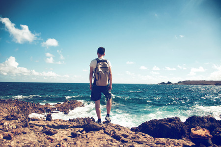 Young man wearing a backpack standing on rocks overlooking the ocean looking down at the white surf in contemplation backlit by the flare of a hot tropical sun