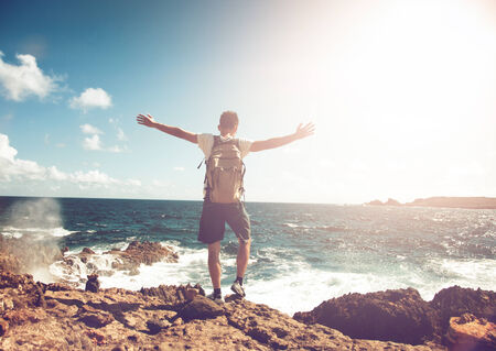Young man wearing a backpack standing on rocks overlooking the ocean with his arms spread in contemplation backlit by the flare of a hot tropical sun photo