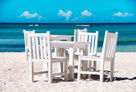 Idyllic outdoor dining on a tropical beach in Aruba with fresh white painted wooden table and chairs on clean white sand alongside a calm azure blue ocean in hot summer sunshine photo
