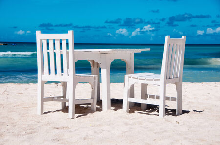 dining table and chairs: Idyllic outdoor dining on a tropical beach in Aruba with fresh white painted wooden table and chairs on clean white sand alongside a calm azure blue ocean in hot summer sunshine