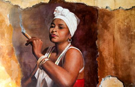 Mujer en Aruba que llevaba un pañuelo en la cabeza y joyería tradicional fumando un gran cigarro cubano gordo con una mirada de entusiasmo y desafío contra un viejo grafiti grunge pared pintada de marrón