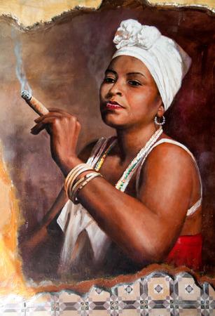 cigarro: Mujer en Aruba que llevaba un pañuelo en la cabeza y joyería tradicional fumando un gran cigarro cubano gordo con una mirada de entusiasmo y desafío contra un viejo grafiti grunge pared pintada de marrón
