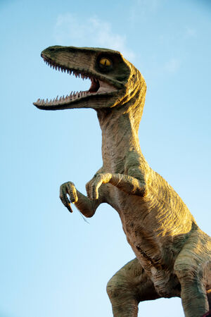 monstrous: Tyrannosaurus rex or T-rex model rearing up with an open mouth against a blue sky in a reconstruction of the world of dinosaurs