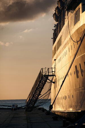disembarking: View along the dock and side of the ship of a metal passenger staircase and gangway on a cruise liner fro embarking and disembarking with an ocean bacldrop at sunset Stock Photo