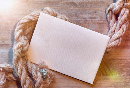cordage: Nautical maritime background with cordage on weathered wood with blank white card and copyspace