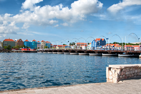 dutch landmark: Scenic view of Willemstad , Curacao, Dutch Antilles, waterfront with its traditional historical buildings and curving lampposts under a cloudy blue sunny sky Editorial