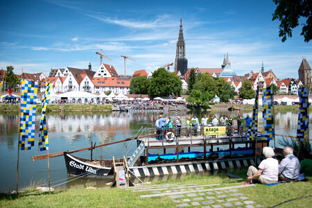 Elderly couple sitting on the banks of the Danube River in Germany overlooking the picturesque town of Ulm in front of a tour boat