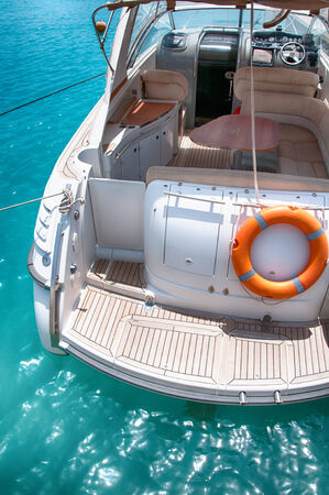 super yacht: Landing deck on the back of a luxury motorboat moored in a sparkling blue marina with a life buoy and view of the interior of the cabin