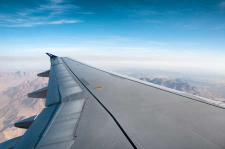 View along the wing of an airplane from the passengers perspective flying over mountainous terrain with a hazy sunny blue sky above photo