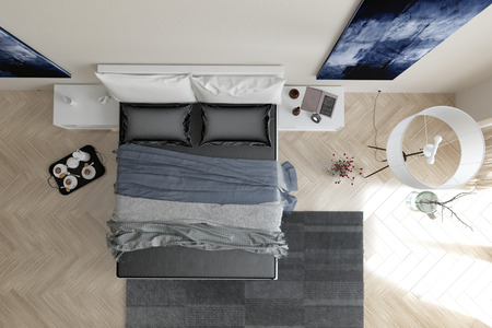 Overhead view of modern grey and white bedroom interior with a double bed with throws and a padded headboard, wall art, grey carpet, lamp and coffee tray on a herringbone pattern parquet floor Stock Photo
