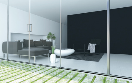 home accents: Modern living room viewed from a patio through a floor to ceiling glass wall or windows with an upholstered lounge suite and minimalist grey and white decor Stock Photo