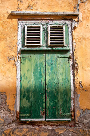 deteriorating: Old window with weathered green wooden shutters in a grungy exterior wall of a building with damaged plaster and paint, architectural
