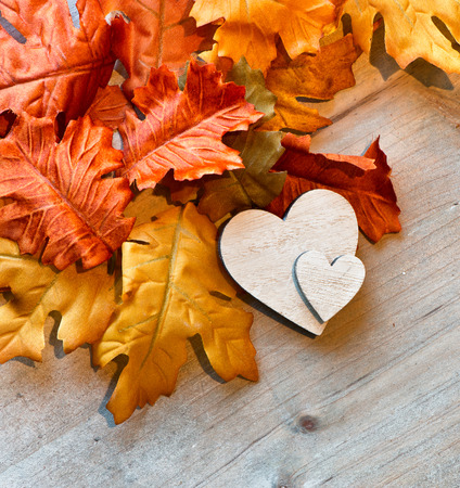 Wooden Hearts and Autumn Leaves on Wooden Background as seen from Above Stock Photo
