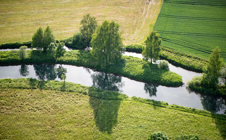 Aerial view from above of a scenic landscape with a river dividing around an island with trees in rural farmland photo