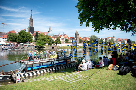 Group of people sitting in the shade on the banks of the River Danube overlooking the scenic town of Ulm in Germany