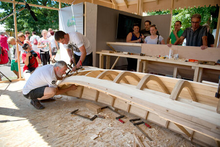 Boat builder and designer working on a hand crafted wooden boat at a festival in Ulm Germany on the Danube River watched by a group of spectators