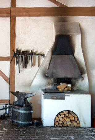 forge: Rustic interior in an old forge with a wood burning oven, tools hanging on the wall and old metal anvil