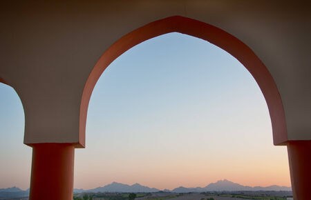 View of Red Sea Mountains at Dusk as seen through Arched Window photo