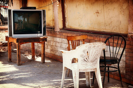Variety of Chairs Set in front of Television Outdoors