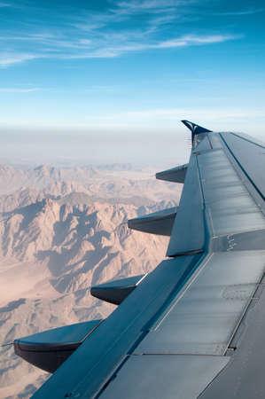plan éloigné: Vue de l'aile d'un avion en vol depuis le point de vue des passagers survolant terrain montagneux dans un ciel bleu ensoleillé