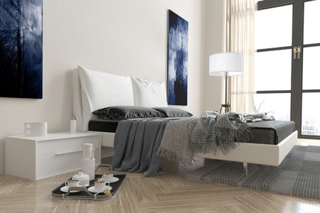 Modern bedroom interior with double divan bed covered in rugs and throws in grey and white decor with a breakfast tray on the floor alongside and a window behind Stock Photo