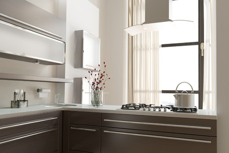 Modern open-plan kitchen with built in hob on an open counter facing a large bright window and wall mounted built in cabinets and appliances, grey and white interior decor photo