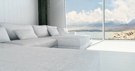 Living room interior with a view of the ocean and mountains through large windows from a white upholstered longe suite