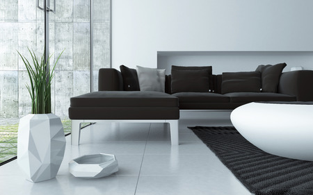 Modern grey and white living room interior viewed low angle over a tiled floor with an upholstered lounge suite , stylish contemporary coffee table and ornamental pot plant in front of large windows Фото со стока