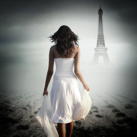 Rear view of a woman walking towards the Eiffel tower photo
