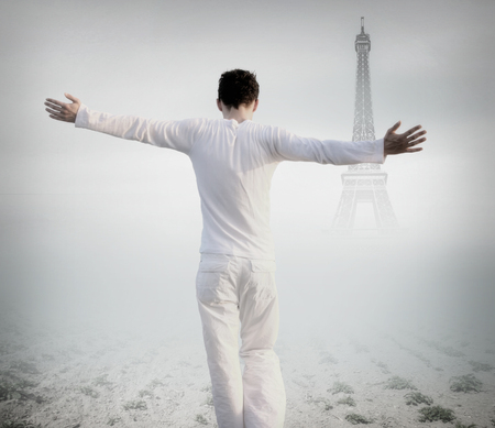Rear view of a man with open arms facing the Eiffel tower photo
