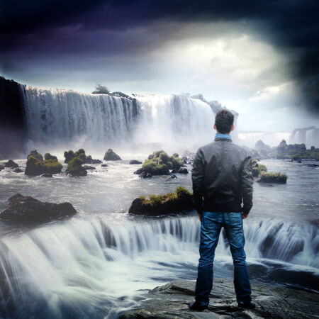 deep thought: Rear view of a man facing a huge waterfall