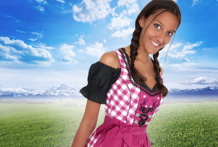 Young woman in dirndl smiling in the field photo