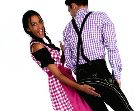Playful couple in traditional Bavarian clothes posing on white background photo