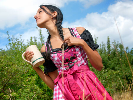 Young woman wearing dirndl posing with beer mug in the field photo