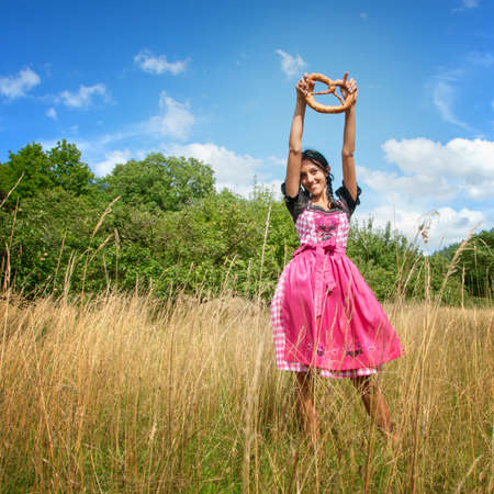 Young woman in dirndl holding a pretzel and posing in the field photo
