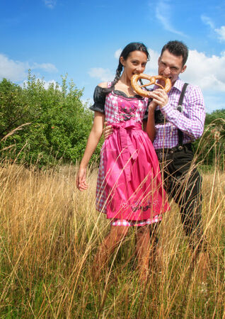 Young couple in traditional Bavarian clothes biting a pretzel in the field photo