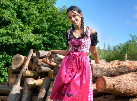 Young woman in dirndl posing in front of a pile of logs photo