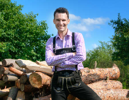 Young man in traditional Bavarian clothes posing in front of a pile of logs photo