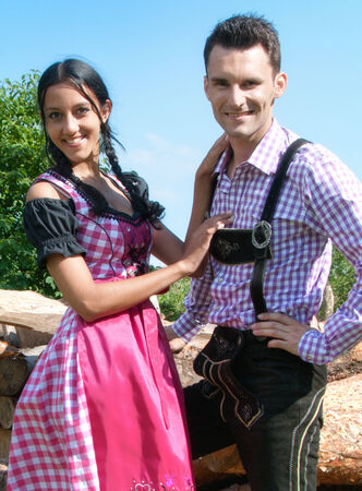 Young couple in traditional Bavarian clothes posing in front of a pile of logs photo