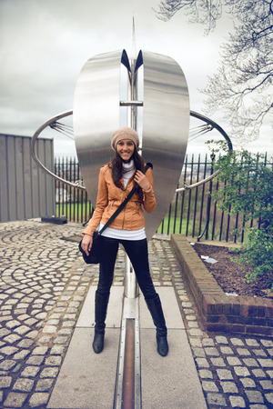 0 geography: Smiling young woman tourist straddling the prime meridian line for zero degrees longitude at greenwich, London with one foot in the easter and one in the western hemisphere