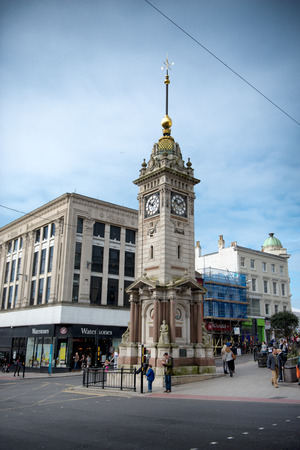 erected: Brighton Clocktower, a freestanding clocktower erected in 1888 to commemorate the Jubilee of Queen Victoria, standing at the intersection of two thoroughfares with people walking on the sidewalk Editorial
