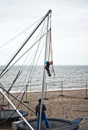 bungee jumping: Niño en el trampolín Bungee Jumping en Shores of Brighton Beach, Brighton, Inglaterra