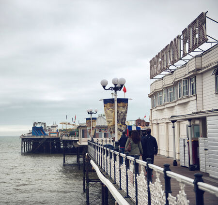 People walking on the decking on Brighton Pier passing below the sign on their way to the amusement park , view along the ornate white railing