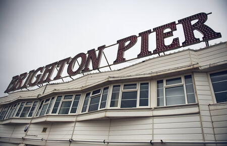 Brighton Pier sign on the rooftop of an old wooden Victorian building on the Grade 1 listed Palace Pier in Brighton, East Sussex, UK