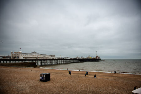 listed buildings: View of the beach and Brighton Pier with groups of people on the sand and the historical wooden buildings on the Palace Pier dating from the Victorian era and now a listed landmark