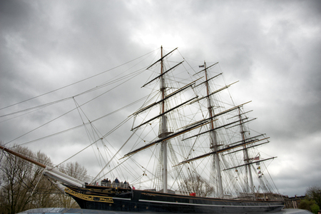 View of the Cutty Sark at Greenwich, London, a wooden Victorian three-masted merchant clipper now a museum exhibit on a cloudy grey day Editorial