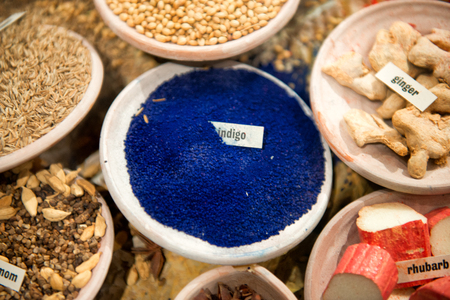 rhubarb: Bowl of natural blue indigo dye with root ginger, rhubarb herbs and spices displayed on a stall at market, view from above Stock Photo