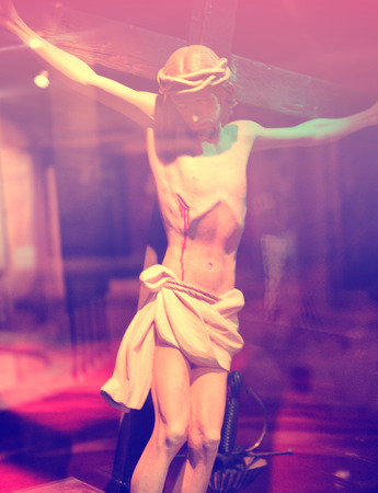 executed: Close Up of Crucifixion Statue with Dramatic Pink Lighting Stock Photo